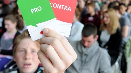 Ein Schüler hält während einer Veranstaltung der Landeszentrale für politische Bildung. (Archivbild)