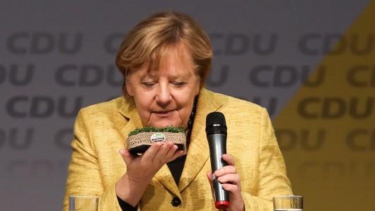 Bundeskanzlerin Angela Merkel (CDU) riecht bei einer Wahlkampfveranstaltung in Seevetal an einem Körbchen mit Kresse.