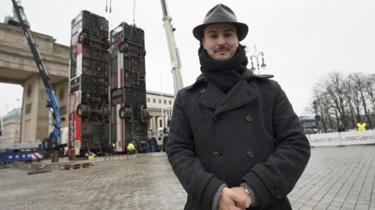 Der deutsch-syrische Künstler Manaf Halbouni steht in Berlin vor dem Brandenburger Tor vor zwei ausrangierten Bussen, die vor dem Tor aufgestellt werden.
