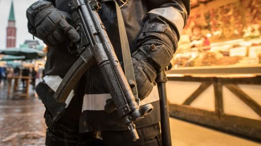 Ein mit einer Maschinenpistole bewaffneter Polizist bewacht einen Weihnachtsmarkt. (Archivbild)