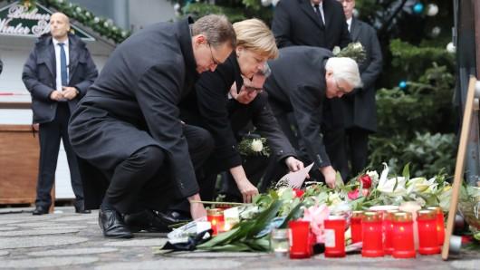 Bundeskanzlerin Angela Merkel (CDU) gedenkt  am Ort des Anschlages in Berlin der Opfer zusammen mit Bundesinnenminister Thomas de Maizière (CDU), dem damaligen Bundesaußenminister Frank-Walter Steinmeier (SPD, rechts) und mit dem Regierenden Bürgermeister von Berlin, Michael Müller (SPD, links). (Archivbild)