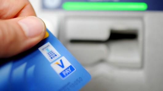 ARCHIV - ILLUSTRATION - Ein Bankkunde hebt am 08.11.2011 in Hamburg mit seiner Girokarte Bargeld von einem Geldautomaten ab. (zu dpa-Berichterstattung über Datenklau an Geldautomaten in Deutschland im Jahr 2017 vom 09.12.2017) Foto: Angelika Warmuth/dpa +++(c) dpa - Bildfunk+++