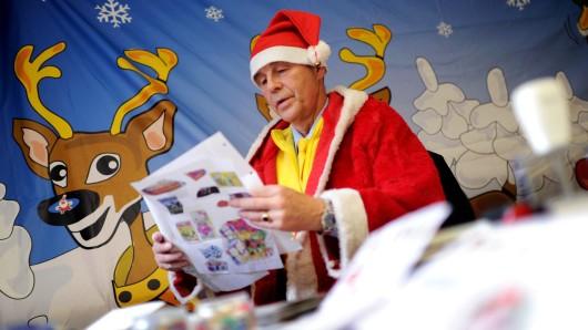 Weihnachtsmann-Gehilfe Karl-Heinz Dünker liest in der Weihnachtspostfiliale im Hildesheimer Stadtteil Himmelsthür Briefe von Kindern. (Archivbild)