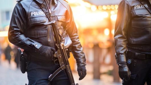 Schwer bewaffnete Polizisten gehen über einen Weihnachtsmarkt in Hildesheim.