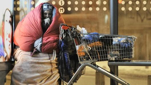In Schlafsack und Decken gehüllt sitzt eine obdachlose Frau in der Nacht an einer Bushaltestelle neben einem Einkaufswagen mit ihren Habseligkeiten. (Archivbild)