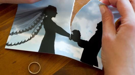 Eine Frau zereisst ihr Hochzeitsfoto. (Symbolbild zum Thema Scheidung)