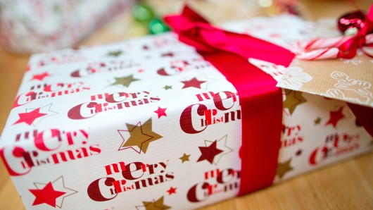 """ARCHIV - Ein Geschenk mit der Aufschrift """"Merry Christmas"""" liegt am 19.12.2013 unter einem Weihnachtsbaum in Köln (Nordrhein-Westfalen). Der Handelsverband Deutschland (HDE) äußert sich am 09.11.2017 zu den Erwartungen der Unternehmen an das Weihnachtsgeschäft. Foto: Rolf Vennenbernd/dpa +++(c) dpa - Bildfunk+++"""