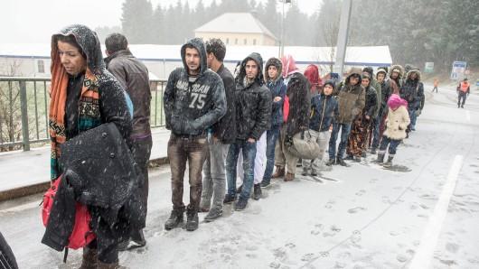 ARCHIV - Flüchtlinge warten am 21.11.2015 an der deutsch-österreichischen Grenze nahe Wegscheid (Bayern) während eines Schneeschauers auf ihre Einreise nach Deutschland. (zu dpa Deutlich weniger Flüchtlinge an der Grenze zu Bayern gestoppt vom 24.12.2017) Foto: Armin Weigel/dpa +++(c) dpa - Bildfunk+++