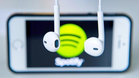 ARCHIV - ILLUSTRATION- Kopfhörer hängen am 17.03.2014 in Berlin vor einem Apple Iphone 5s, auf dem das Logo vom Musik-Streaming-Dienst Spotify angezeigt wird. (zu dpa Milliardenklage gegen Spotify wegen Autorenrechten vom 03.01.2018) Foto: Daniel Bockwoldt/dpa +++(c) dpa - Bildfunk+++