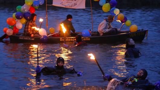 Mit Fackeln und geschmückten Booten schwimmen Teilnehmer des Fackelschwimmens auf der Aller bei Celle. (Archivbild)