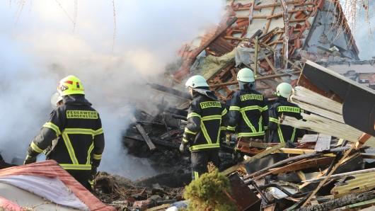 Einsatzkräfte der Feuerwehr löschen den Brand nach einer Wohnhausexplosion in Halberstadt.