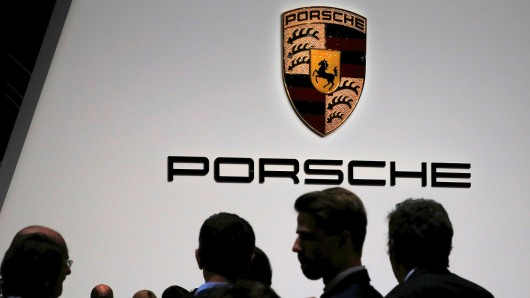 Visitors stand in front of a Porsche logo during the 88th Geneva International Motor Show in Geneva, Switzerland, March 6, 2018. REUTERS/Denis Balibouse