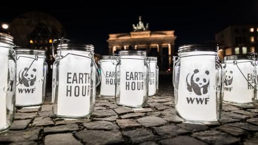 Leuchtende Gläser stehen am Abend vor dem Brandenburger Tor. Im Rahmen der weltweiten Aktion Earth Hour wurde das Licht am Tor ausgeschaltet. Mit der Aktion will die Umweltorganisation WWF für den Klimaschutz werben.
