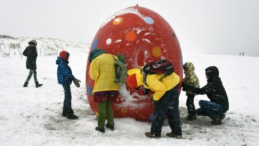 Besucher der Insel Hiddensee bestaunen ein Riesen-Ei, das im Schnee am Strand steht.