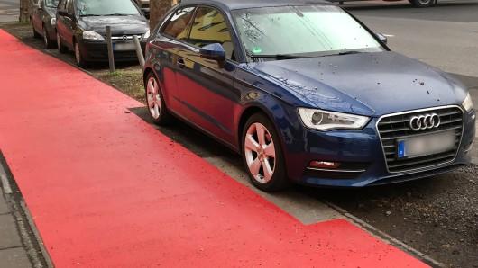 Eine frisch gestrichene Radwegmarkierung spart in Köln ein geparktes Auto aus. Statt das widerrechtlich auf dem Radweg geparkte Fahrzeug abschleppen zu lassen, wurde mit der roten Farbe kurzerhand um das Auto herumgemalt.