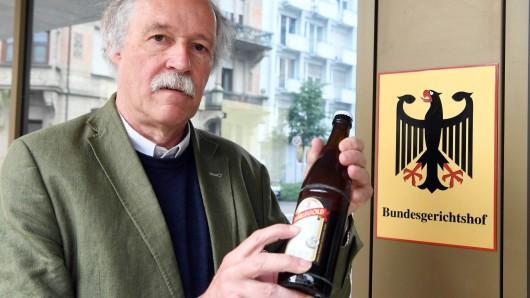 Gottfried Härle, Geschäftsführer der Brauerei Clemens Härle, zeigt vor dem Bundesgerichtshof eine Flasche Bier, auf der das Wort bekömmlich steht.