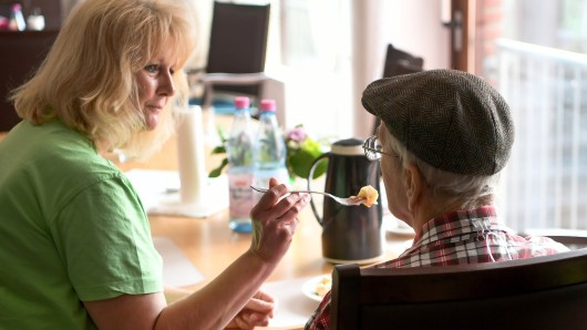 Eine Pflegerin betreut einen älteren Mann während des Frühstücks (Archivbild).