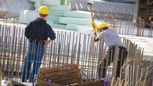 """ARCHIV - 11.03.2015, Hamburg: Männer arbeiten auf einer Baustelle. (zu dpa """"Bauboom, Sparzwang und die Folgen für Natur und Umwelt"""" vom 30.05.2018) Foto: Daniel Reinhardt/dpa +++ dpa-Bildfunk +++"""