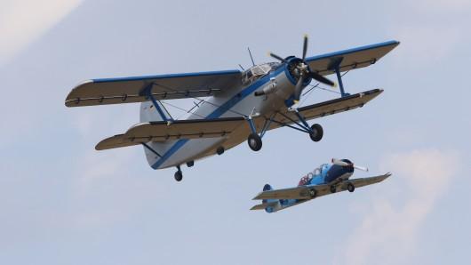 Zwei Motorflugzeuge, ein Doppeldecker AN 2 und eine Jackolew Jak 52, präsentieren eine Flugvorführung auf dem Flugplatz Gardelegen.