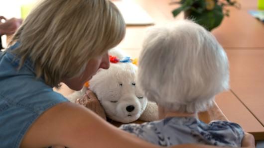 Eine Ergotherapeutin spricht in einem Seniorenpflegeheim für Menschen mit Demenz mit einer älteren Frau.