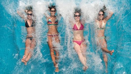 Four beautiful women splashing backwards into a pool. Perfect funny face expressions. Simply letting go. Nikon D3X. Converted from RAW. (XXXL) Schwimmen Schwimmbad Baden Planschen Wasser Abkühlung Sommer Wetter Freibad Frauen Mädchen Sprung Springen Spritzen Pool Becken Symbol Hitze Kühl Wasser