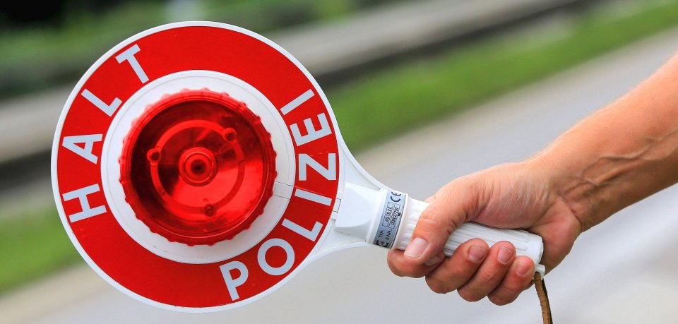 Ein Polizist hält eine Polizeikelle in der Hand mit der Aufschrift Halt Polizei Symbolbild Polizeikontrolle - Halt Polizei a Policeman holds a Polizeikelle in the Hand with the Inscription Maintenance Police Symbol image Police control Maintenance Police