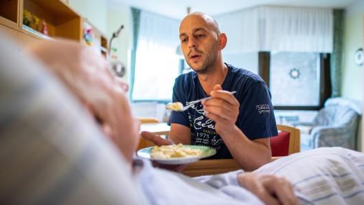 Der Altenpfleger Ferdi Cebi reicht einem Bewohner Nahrung an (Archivbild).