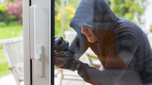 Ein Einbrecher gelangt durchs Fenster in eine Wohnung (Symbolbild).