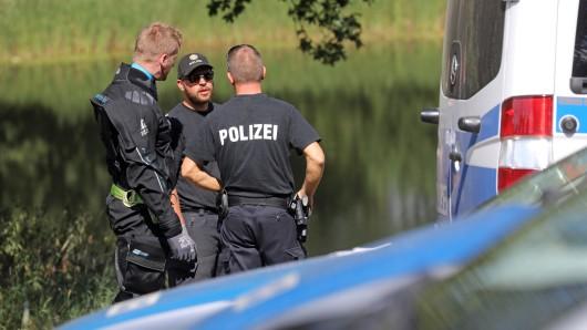 Polizisten stehen am Ufer eines Sees (Archivbild).