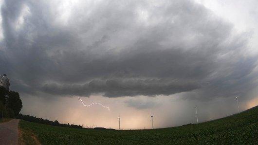 09.08.2018, Niedersachsen, Sehnde: Eine Unwetterfront mit Blitzschlag zieht über ein Feld mit Windrädern hinweg. Schwere Gewitter mit Starkregen und Sturmböen ziehen über Deutschland hinweg. Foto: Julian Stratenschulte/dpa +++ dpa-Bildfunk +++