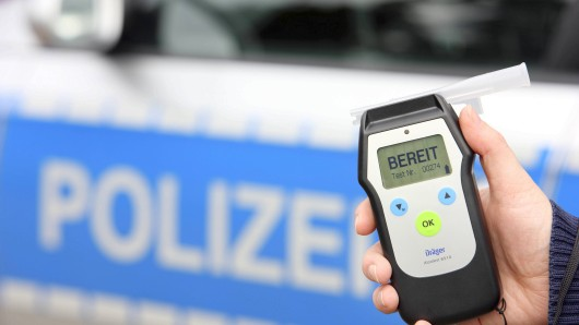 Polizei, Streifenwagen. Polizist mit Atemalkohol Testgerät. Zur Überprüfung der Fahrtüchtigkeit eines Autofahrers. Symbolbild. Polizei Police Patrol car Policeman with Breath Test equipment to Review the Driving a Car driver Symbol image Police