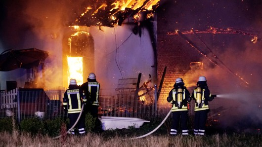 Feuerwehrleute bekämpfen einen Brand. Bei dem Feuer in einem Hundezuchtbetrieb sind am Freitag mehrere Tiere gestorben.
