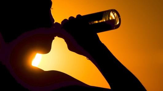 02.07.2018, Niedersachsen, Hannover: Ein junger Mann sitzt biertrinkend auf dem Kronsberg, während am Horizont die Sonne untergeht. Foto: Julian Stratenschulte/dpa +++ dpa-Bildfunk +++