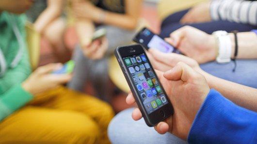 Schueler sitzen zusammen und spielen mit ihren Smartphones. Model Release vorhanden, model released.