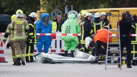 Feuerwehrkräfte stehen bei einem Gefahrstoffeinsatz in einem Paket- und Briefzentrum der Deutschen Post.