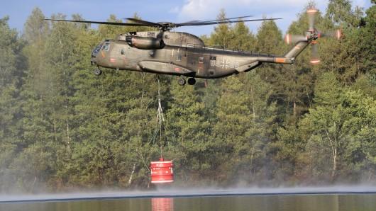 Ein Transporthubschrauber CH-53 der Bundeswehr nimmt auf dem Gelände der Wehrtechnischen Dienststelle 91 in Meppen Wasser zur Bekämpfung eines großflächigen Moorbrands auf.