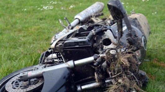 Ein zerstörtes Motorrad liegt am Straßenrand.