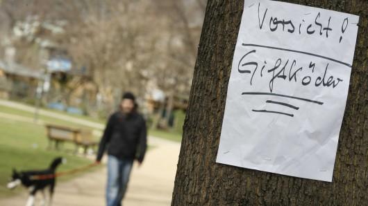 Ein Zettel warnt in einem Park vor Giftködern. (Symbolbild)