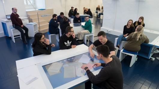 Jungendliche informieren sich an interaktiven Tischen.