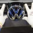 Das VW-Logo wird am Frontgrill an einen Golf angebracht.