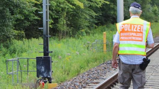 Ein Bundespolizist geht in der Nähe von Berlin auf den Gleisen auf eine beschädigte Signalanlage zu.