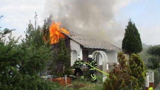 Die Feuerwehr löscht die Flammen, die aus den Fenstern einer Gartenlaube in Vorsfelde schlagen.